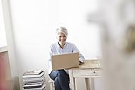 Mature woman sitting at table using laptop - FMKF001461