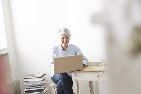 Mature woman sitting at table using laptop - FMKF001461