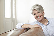 Portrait of smiling mature woman sitting on couch - FMKF001479