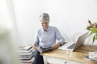Mature woman sitting at table with magazine and laptop - FMKF001483