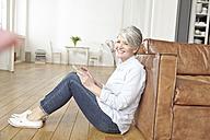 Mature woman sitting on floor using digital tablet - FMKF001485