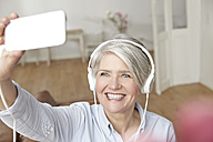 Mature woman wearing headphones taking selfie - FMKF001499