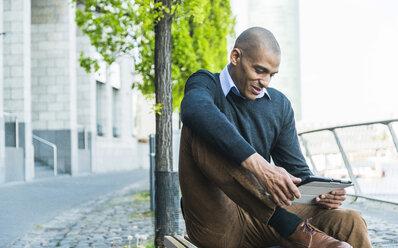 Man sitting on bench using digital tablet - UUF004024