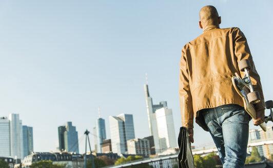 Germany, Frankfurt, man on the go carrying skatebaord and briefcase - UUF004028
