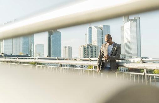 Germany, Frankfurt, businessman on bridge looking on smartphone - UUF004035