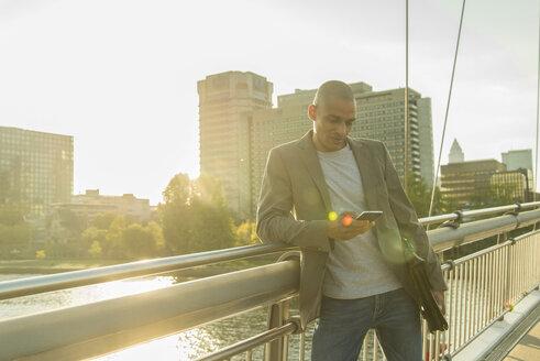 Germany, Frankfurt, businessman on bridge looking on smartphone - UUF004043