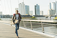 Germany, Frankfurt, man running with skateboard on bridge - UUF004047