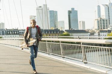 Germany, Frankfurt, man running with skateboard on bridge - UUF004047