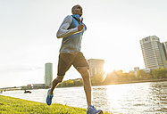 Germany, Frankfurt, man jogging by the riverside - UUF004049