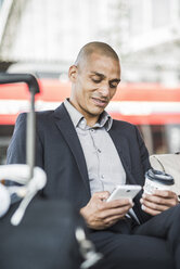 Businessman at the train station looking on smartphone - UUF004056