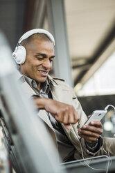 Man wearing headphones holding smartphone - UUF004061
