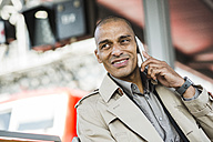 Smiling businessman talking on smartphone - UUF004064