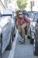 Young man on skateboard in traffic jam - ZEF004902