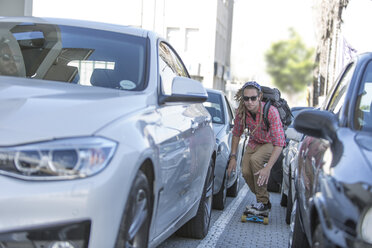 Young man on skateboard in traffic jam - ZEF004613