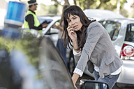 Woman on cell phone at car accident scene - ZEF004760