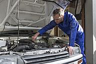 Man working on car in home garage - ZEF004812