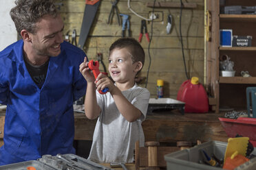 Father and son working in home garage - ZEF004818
