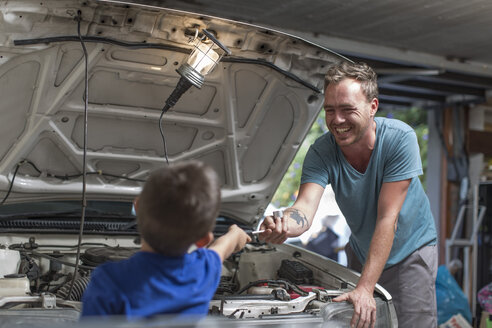 Son helping father in home garage working on car - ZEF004823