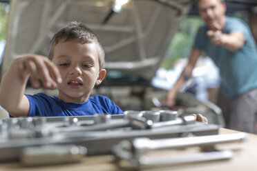 Son helping father in home garage working on car - ZEF004824