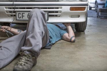 Mechanic lying on floor working on car - ZEF004879