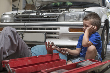 Son helping father in home garage working on car - ZEF004880