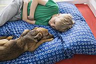 Boy and dog lying on bed - PDF000917