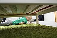 Boy using digital tablet on carpet beside bed - PDF000929