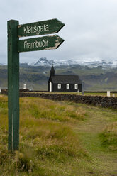 Iceland, Budir, view to church  with sign post in the foreground - KEBF000183