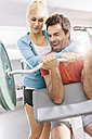 Young couple training with EZ curl bar at gym - MADF000199