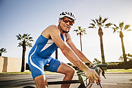 Spain, Mallorca, Sa Coma, smiling triathlet training on bicycle - MFF001601