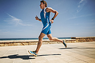 Spain, Mallorca, Sa Coma, triathlet running along beach promenade - MFF001617