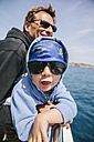 Spain, Mallorca, little boy wearing sunglasses and pirate bandana and his uncle on a sailing boat - MFF001585