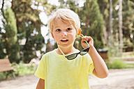 Spain, Mallorca, portrait of blond little boy holding sunglasses - MFF001596