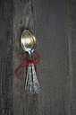 Old silver spoons tied together with red thread on dark wood - CRF002683