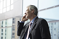 Businessman standing at window using mobile phone - RBF002657