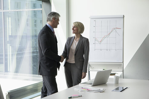 Businissman and businesswoman shaking hands in conference room - RBF002660