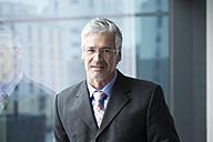 Businessman standing at window, portrait - RBF002662