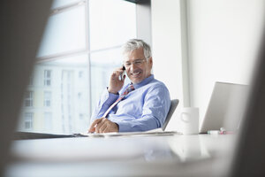 Businessman sitting at desk, talking on the phone - RBF002680
