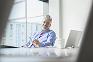 Businessman sitting at desk - RBF002682