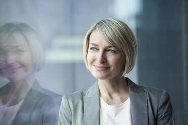 Businesswoman standing at window, smiling, portrait - RBF002688