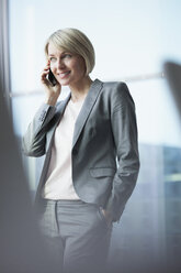 Businesswoman standing at window using mobile phone - RBF002691
