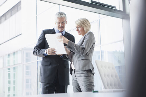 Businissman and businesswoman discussing documents - RBF002697