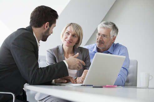 Businesspeople in informal meeting discussing new strategies - RBF002744