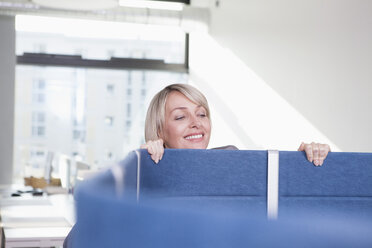 Businesswoman looking over partition in office - RBF002733