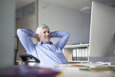 Businessman sitting at desk, hands behind head - RBF002740