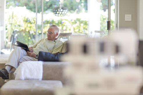 Senior man on sofa looking at tablet - ZEF004839