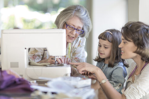 Mother, daughter and grandmother working on sewing machine - ZEF004844