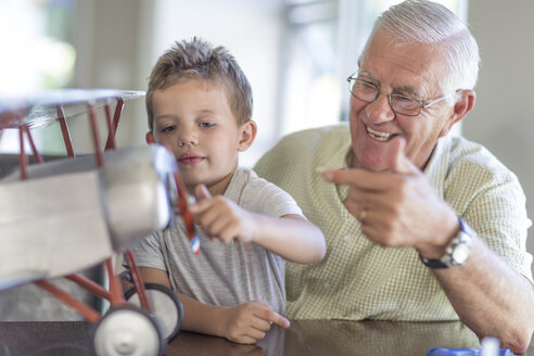 Grandfather and grandson building up a model airplane - ZEF004848