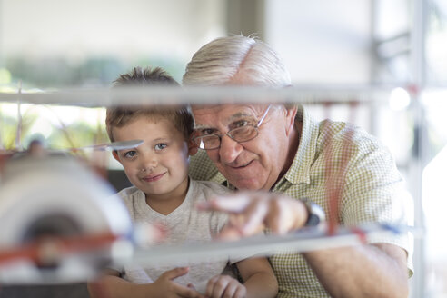 Grandfather and grandson building up a model airplane - ZEF004849