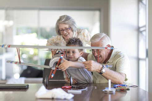 Grandfather and grandson building up a model airplane watched by grandmother - ZEF004850